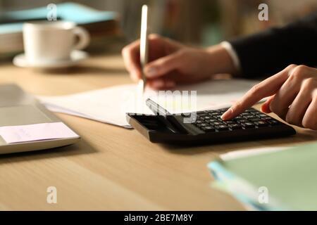 Gros plan sur la comptabilité des mains d'une femme d'affaires à l'aide de la calculatrice la nuit sur un bureau à la maison