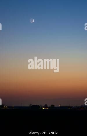 Ciel crépuscule coloré avec petite lune de faucille Banque D'Images