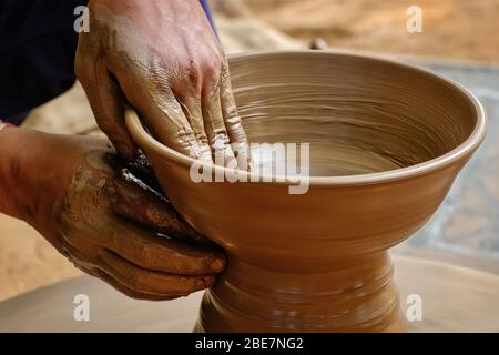 Poterie - mains humides et habiles de potter façonnant l'argile sur la roue de potter