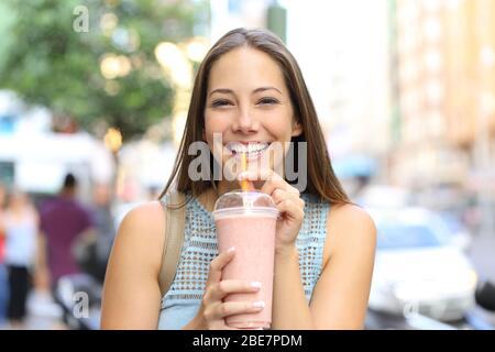 Vue avant portrait d'une heureuse fille regardant appareil photo boire milkshake dans la rue Banque D'Images