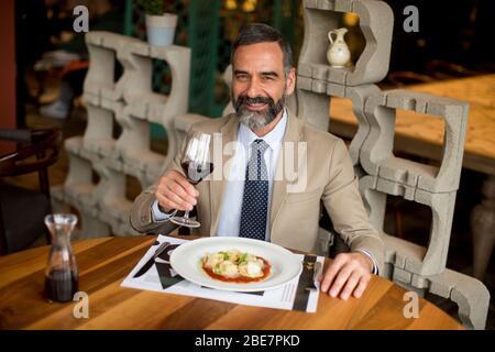 Bel homme mûr buvant du vin rouge pendant le déjeuner au restaurant Banque D'Images