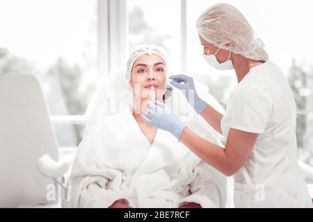 Tiré dans la lèvre. Le cosmologiste porte des gants bleus et un uniforme blanc faisant une photo de beauté dans la lèvre Banque D'Images