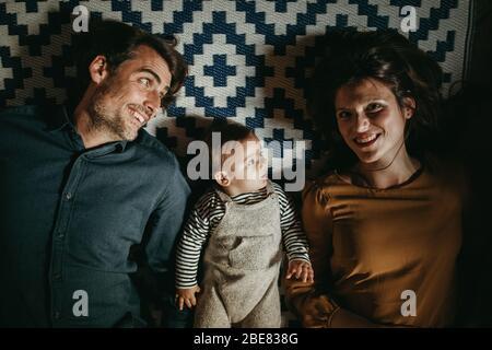 Jeune couple avec leur fils allongé sur le sol à la maison, pendant les loisirs dans le salon.