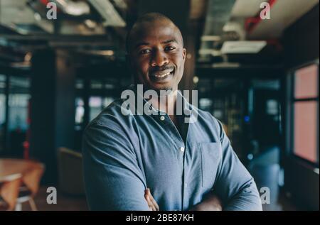 Homme d'affaires confiant au bureau. Un homme africain debout avec ses bras a croisé regarder la caméra et sourire.