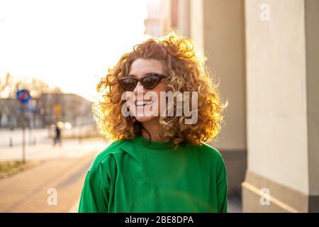 Portrait de la jeune femme avec des cheveux frisés dans la ville