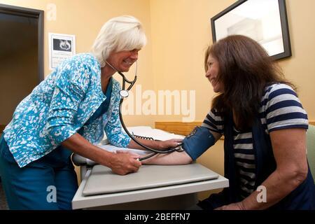 Une infirmière prend de la tension artérielle d'une femme d'âge moyen dans la salle de clinique Banque D'Images