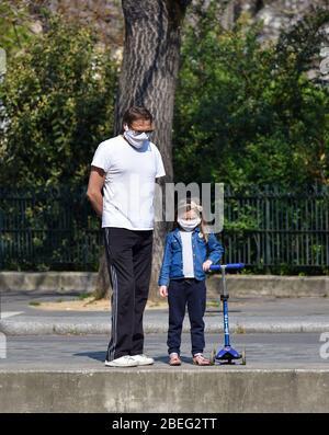 Un père et sa fille marchant dans les rues de Paris, portant un masque de visage en tissu maison pendant la quarantaine déclarée en France. Banque D'Images