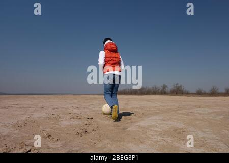 Un garçon de 10 ans dans un sweat-shirt blanc et un gilet orange joue au football sur une plage déserte en solitude. Banque D'Images
