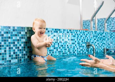 Un petit garçon mignon et amusant assis sur un tuyau en argent dans la piscine se préparant à sauter dans l'eau aux mains de sa mère. Concept de chindhood sain Banque D'Images