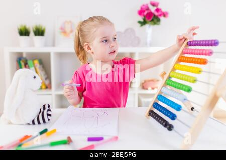 Petite fille blonde souriante assise au bureau blanc et comptant sur l'abacus coloré dans la salle de classe. Éducation préscolaire