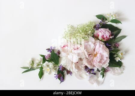 Printemps, composition florale botanique d'été, coin décoratif. Les fleurs roses de pivoine, la sauge, les herbes de fleur de sureau et les branches florantes de philadphus isolent Banque D'Images