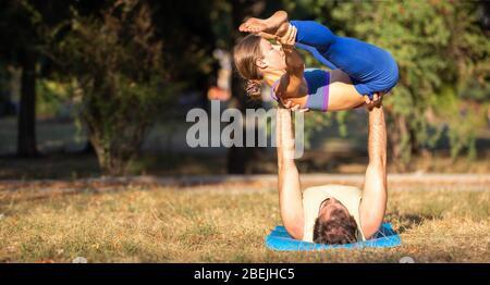 Jeune couple sportif faisant des exercices d'acroyoga à l'extérieur avec espace de copie