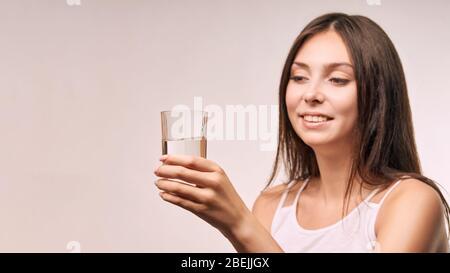 Jeune fille magnifique qui tient du verre d'eau. Hydrate visage femelle. Les femmes heureuses à l'intérieur