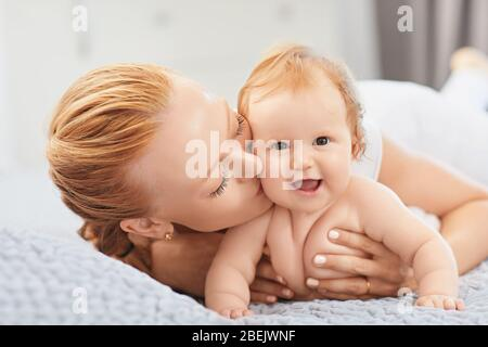 Bonne mère sourit à bébé allongé sur le lit dans la chambre. Banque D'Images