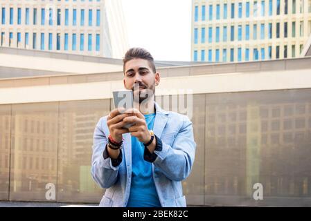 Portrait de beau jeune homme souriant quand il utilise son téléphone mobile Banque D'Images