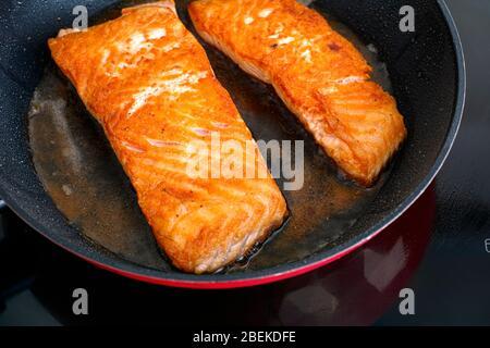 Filets de saumon dans la poêle à frire sur table à induction. Gros plan.