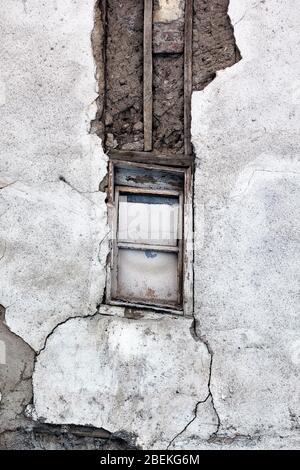 Fenêtres à bord et murs sales épluchés fissurés d'un vieux bâtiment abandonné. Banque D'Images