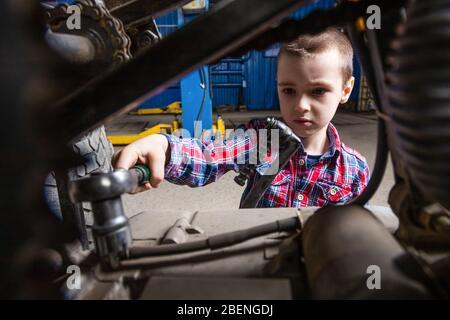 Le garçon rêve de devenir adulte et de réparer des voitures. Le garçon, un jeune travailleur automobile, dévisse les écrous avec une clé dans le garage d'un personnel de service