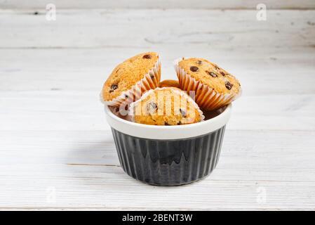 Petits muffins avec des copeaux de chocolat dans un bol sur le fond blanc rustique en bois Banque D'Images