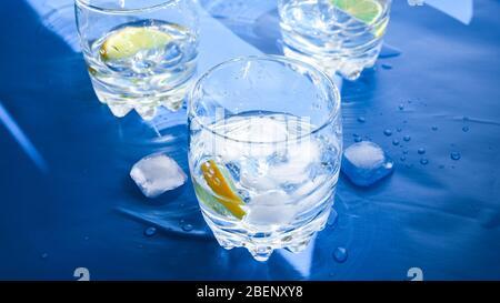 Verres d'eau rafraîchissante avec glace et citron sur fond bleu. Concept de chaleur, frais. Lumière naturelle, espace de copie