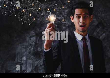Débloquez l'idée et l'accès à la réussite dans le monde des affaires, homme d'affaires tenant l'ampoule et surpris de savoir comment être débloquez.