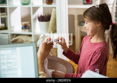 Enfants jouant et perturbant père travaillant à distance de la maison. Petite fille appliquant du vernis à ongles sur les ongles. Homme assis sur un canapé avec ordinateur portable. Famille