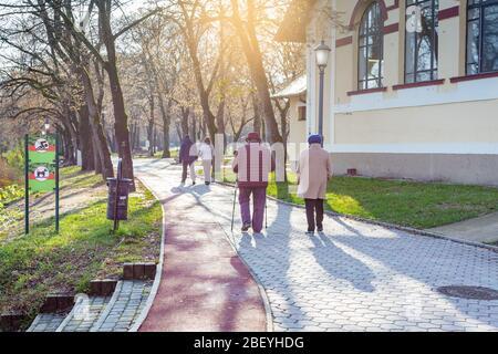 Les femmes âgées et les jeunes couples marchent le long du chemin du parc. Une des femmes utilisant des bâtons de marche nordique. Nyiregyhaza, Hongrie Banque D'Images