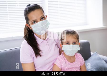 Mère triste et fille au masque à la maison sur la quarantaine du coronavirus