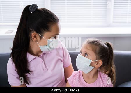 Mère et fille au masque à la maison sur la quarantaine du coronavirus