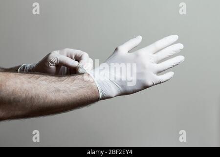 Un closeup d'une main de la mans mettant sur des gants en latex. Banque D'Images