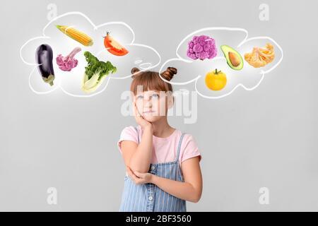 Petite fille imaginant différents légumes sains sur fond clair Banque D'Images