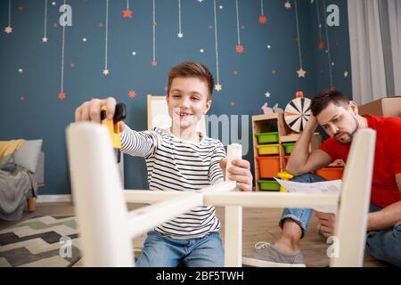 Père et son petit fils assemblant des meubles à la maison Banque D'Images
