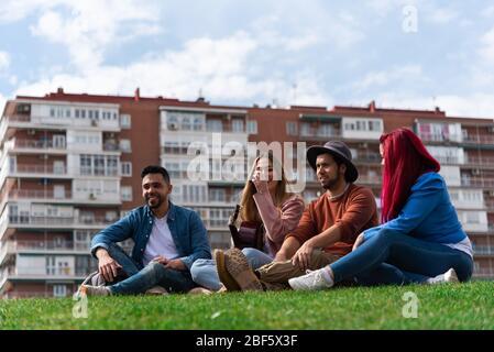 Deux jeunes hommes hispaniques aiment la musique avec une guitare à côté de deux filles caucasiennes dans un parc de la ville, l'image inclut l'espace pour le texte