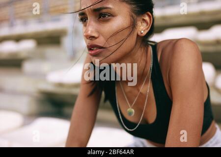 Gros plan d'une athlète féminine qui se fatigue après une séance d'entraînement au stade de sport. Une femme après une course sur la piste du stade.