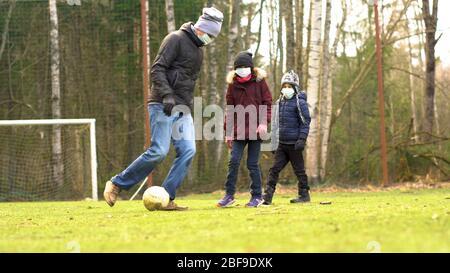 La famille joue au football sur le terrain de jeu pendant la quarantaine de Covid-19. Père avec enfants portant un masque médical pour protéger contre le virus Corona. Banque D'Images