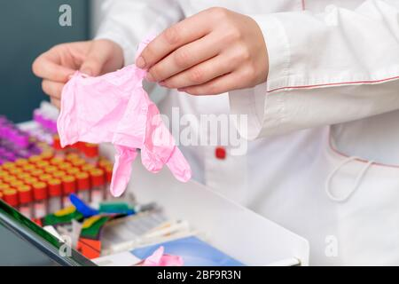 Les mains du médecin mettent des gants en latex rose à l'hôpital, en gros plan. Banque D'Images