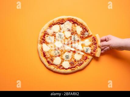 Pizza Quattro formaggi et une femme prennent une tranche de pizza, sur un fond orange sans couture. Plat avec 4 pizzas au fromage. Délicieux plats italiens Banque D'Images