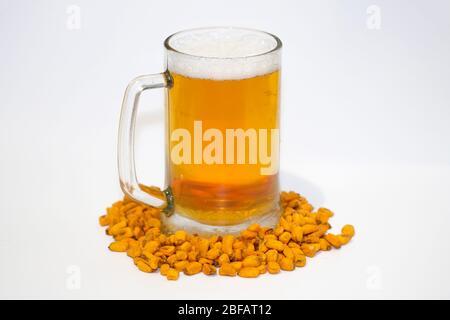 Bière de blé dans un gobelet en verre sur fond blanc. Bière légère et grains de maïs. Bière et collation. Banque D'Images