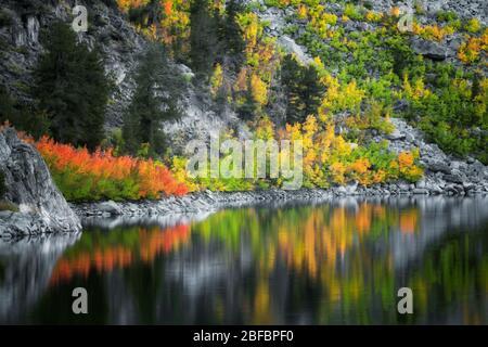 La lueur du crépuscule civil des couleurs d'automne qui s'est rebutée dans le lac Sabrina, entre la chaîne de montagnes de la Sierra orientale de Californie et la forêt nationale d'Inyo.