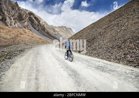 Man on mountain bike rides sur la route dans les hautes montagnes contre fond de ciel bleu. Banque D'Images