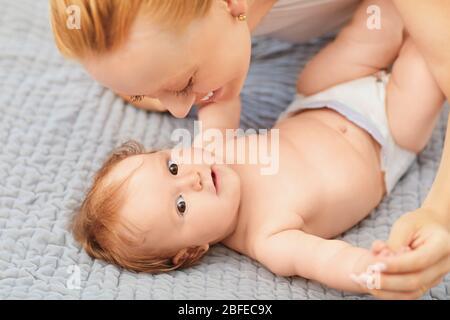 Bonne mère sourit à bébé allongé sur le lit dans la chambre.