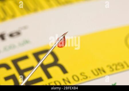 Une goutte de sang visible à l'extrémité de l'aiguille est prête à être éliminée dans un récipient jaune pour les « harpes ». (Medicamage)(modèle libéré) Banque D'Images