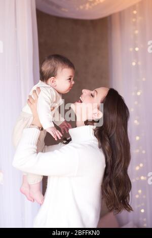 Rire de la mère s'amuser avec un bébé garçon de moins de 1 an dans la chambre. Regarder les uns les autres. Enfance. Maternité. Banque D'Images