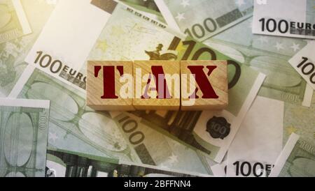 Blocs en bois avec taxe de mot sur 100 billets en euros. Concept comptable de financement des impôts