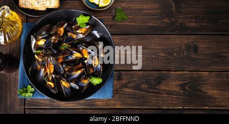 Vue de dessus des moules cuites à la vapeur dans une assiette noire arrière-plan rustique en bois Banque D'Images