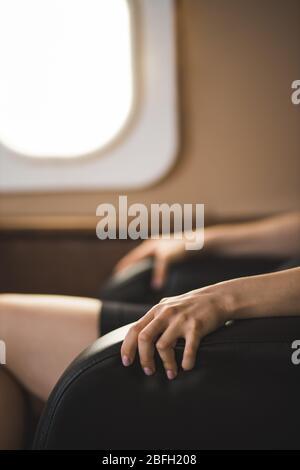 Photo verticale courte d'une femme d'affaires avec peur de vol dans un jet privé. Foyer sélectif de la femme terrifiée assis encombrer les bras de la chaise dedans