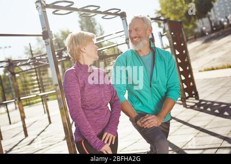 Préchauffage. Heureux couple de famille mûr dans les vêtements de sport faisant la gymnastique ensemble au stade. Homme et femme faisant des exercices d'étirement à l'extérieur