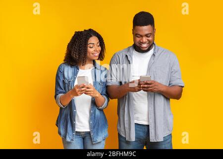 Curieuse petite amie noire qui s'épluche dans le smartphone de mon ami, essayant de lire des messages Banque D'Images