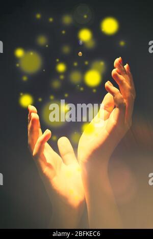 Lumière dans les mains humaines dans le concept sombre et miracle Banque D'Images