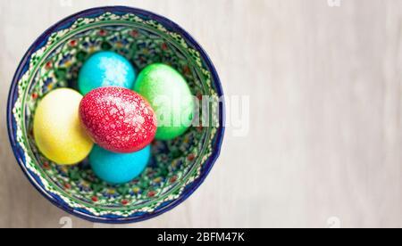 Œufs de Pâques colorés dans un bol sur fond blanc naturel en bois. Vue de dessus. Pose plate.